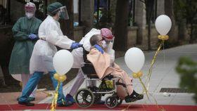 Una anciana en silla de ruedas recibe el cariño del personal sanitario en una residencia.
