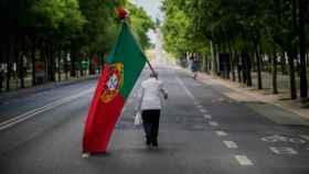 Un ciudadano porta una bandera portuguesa en una avenida solitaria.