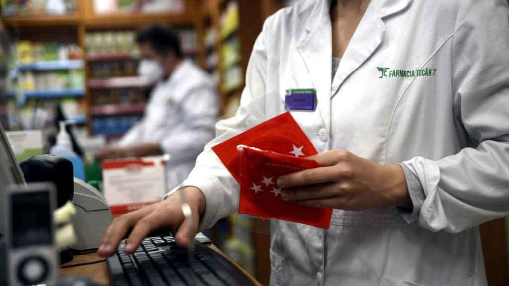 Un farmacéutico dispensando mascarillas en la Comunidad de Madrid.