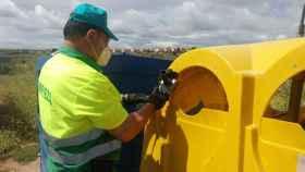 Un operario del Ayuntamiento de Toledo amplía la boca de uno de los contenedores