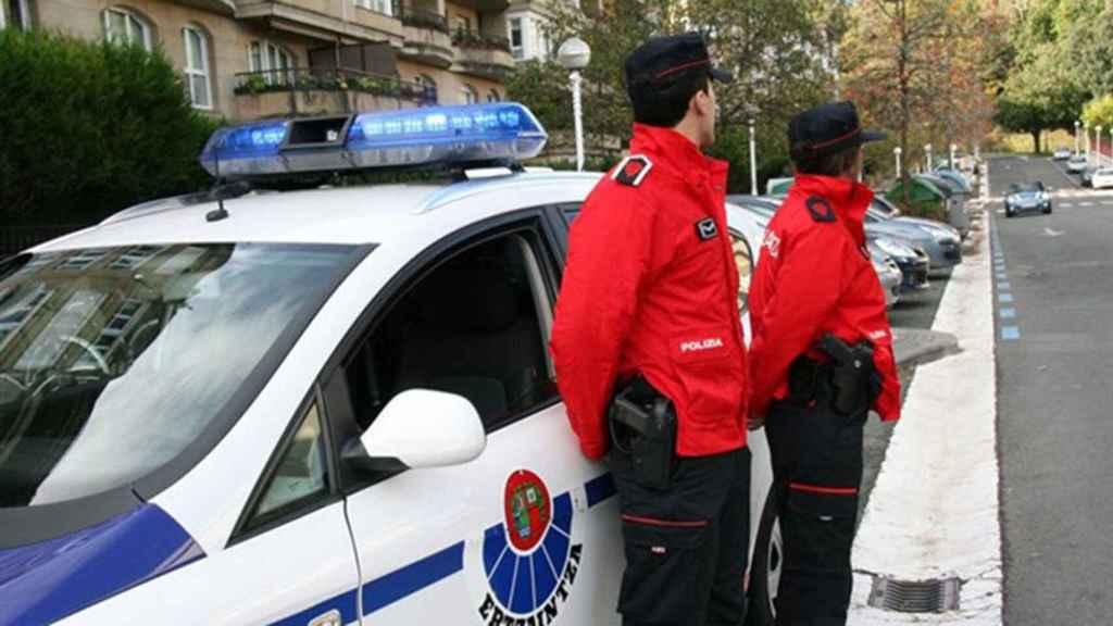 Dos agentes de la Ertzainza, la policía autonómica vasca, junto a su vehículo.