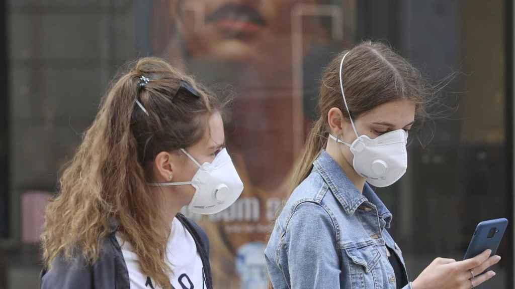 Dos jóvenes llevan mascarillas con válvula en la calle.
