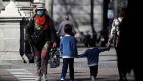 Niños y adultos con mascarillas andando por la calle.