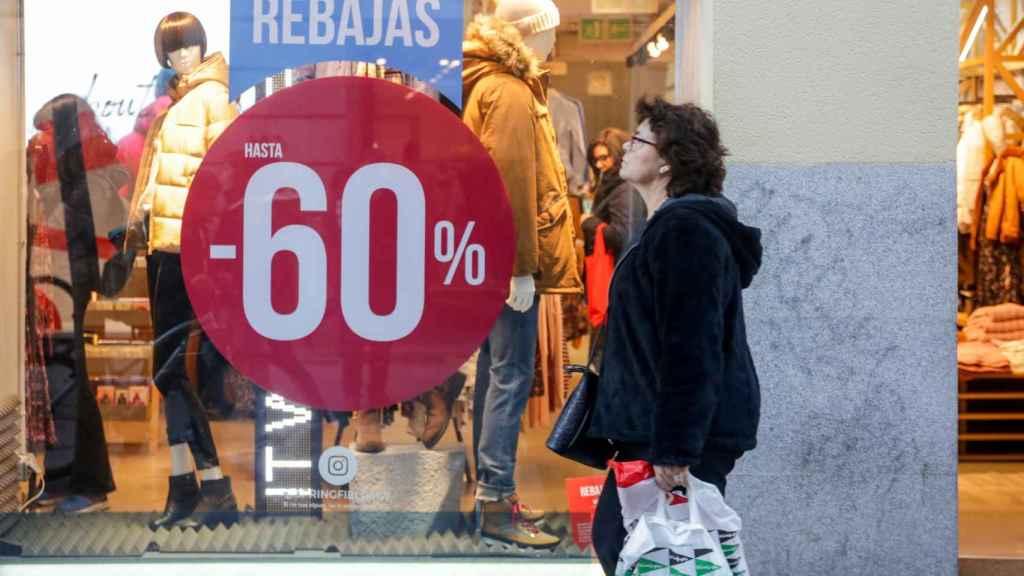 Una mujer pasea junto a una tienda de moda de Madrid, en la que se ofertan las segundas rebajas.