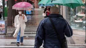 Varias personas se protegen de la lluvia este jueves 14 de mayo en Murcia.