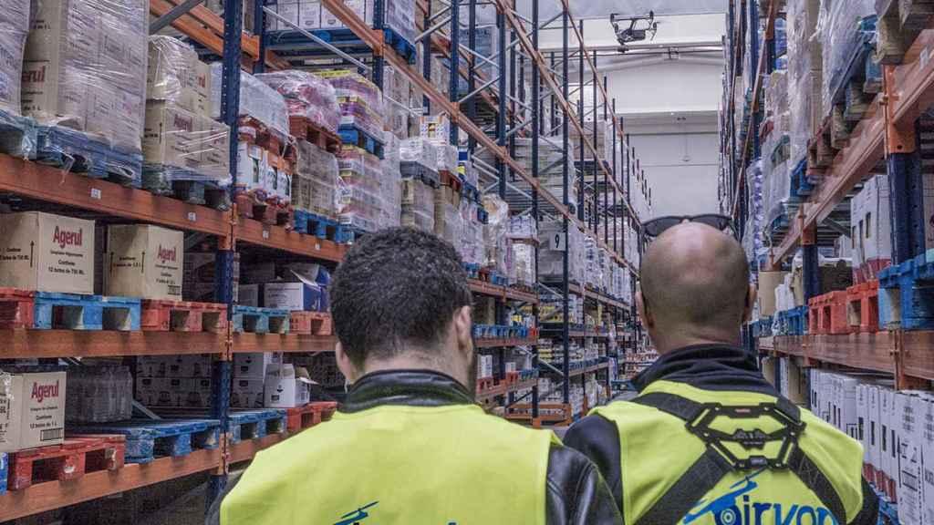 Dos operarios de Airvant con uno de sus drones en un almacén de mercancías.