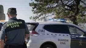Un agente de la Guardia Civil y su coche uniformado.