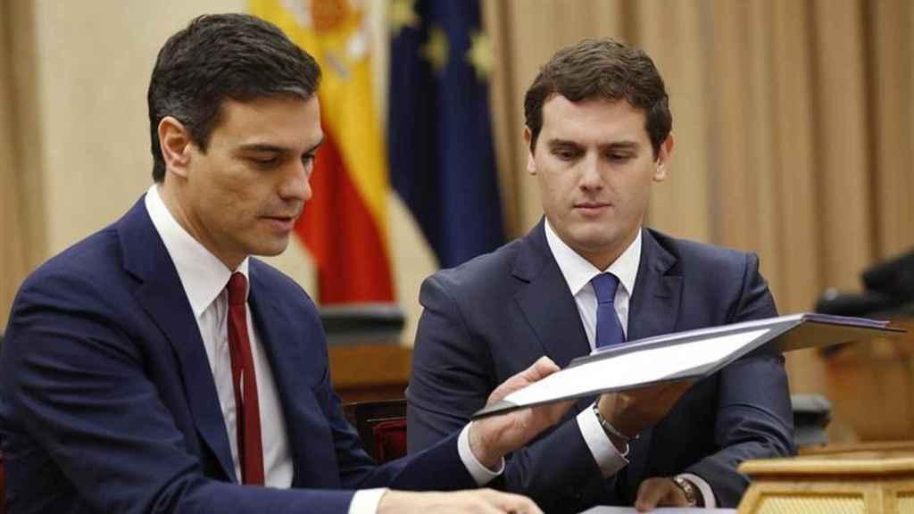 Sánchez y Rivera firmando el pacto del abrazo.