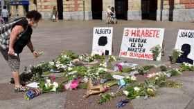 Una mujer deposita fotos en memoria de los dos trabajadores, frente al Ayuntamiento de Eibar.