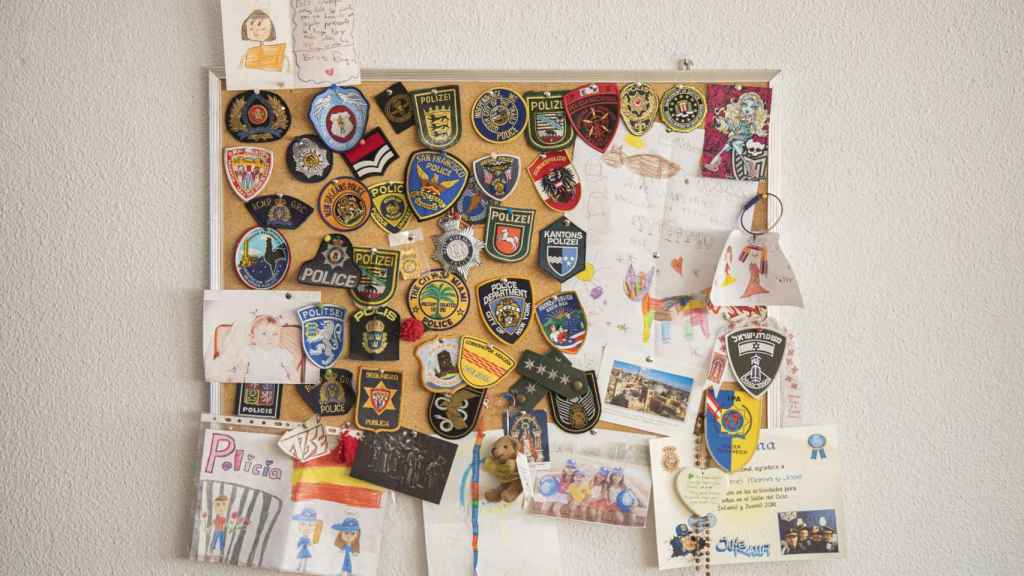 Lo dibujos de sus sobrinas junto a los parches de polícia de distintas ciudades del mundo.