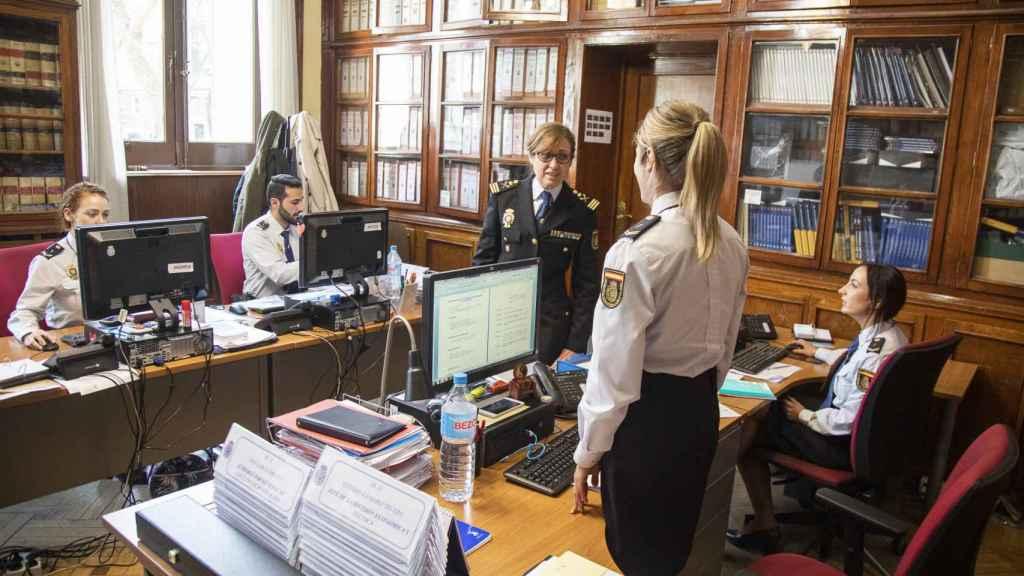 La comisaria charla con dos agentes.