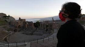 Una mujer con una mascarilla protectora se encuentra en el teatro greco-romano de Taormina, Sicilia.