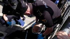 Dos policías españoles atienden a un anciano el viernes pasado en Melilla, durante la repatriación de marroquíes.