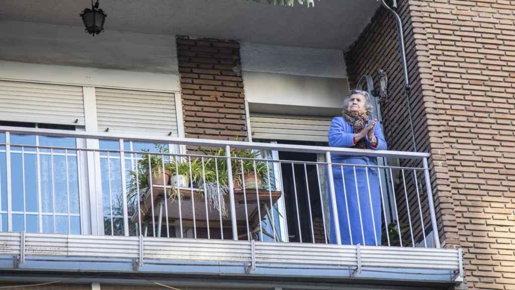 Una mujer aplaude desde su balcón a los sanitarios por última vez.