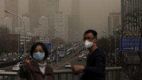 Un hombre y una mujer se protegen con máscaras de la nube de contaminación que cubre la ciudad de Pekín (China).