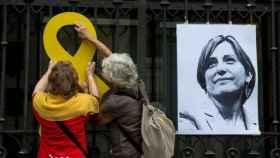 Dos mujeres colocan un lazo amarillo junto a un retrato de Carme Forcadell./