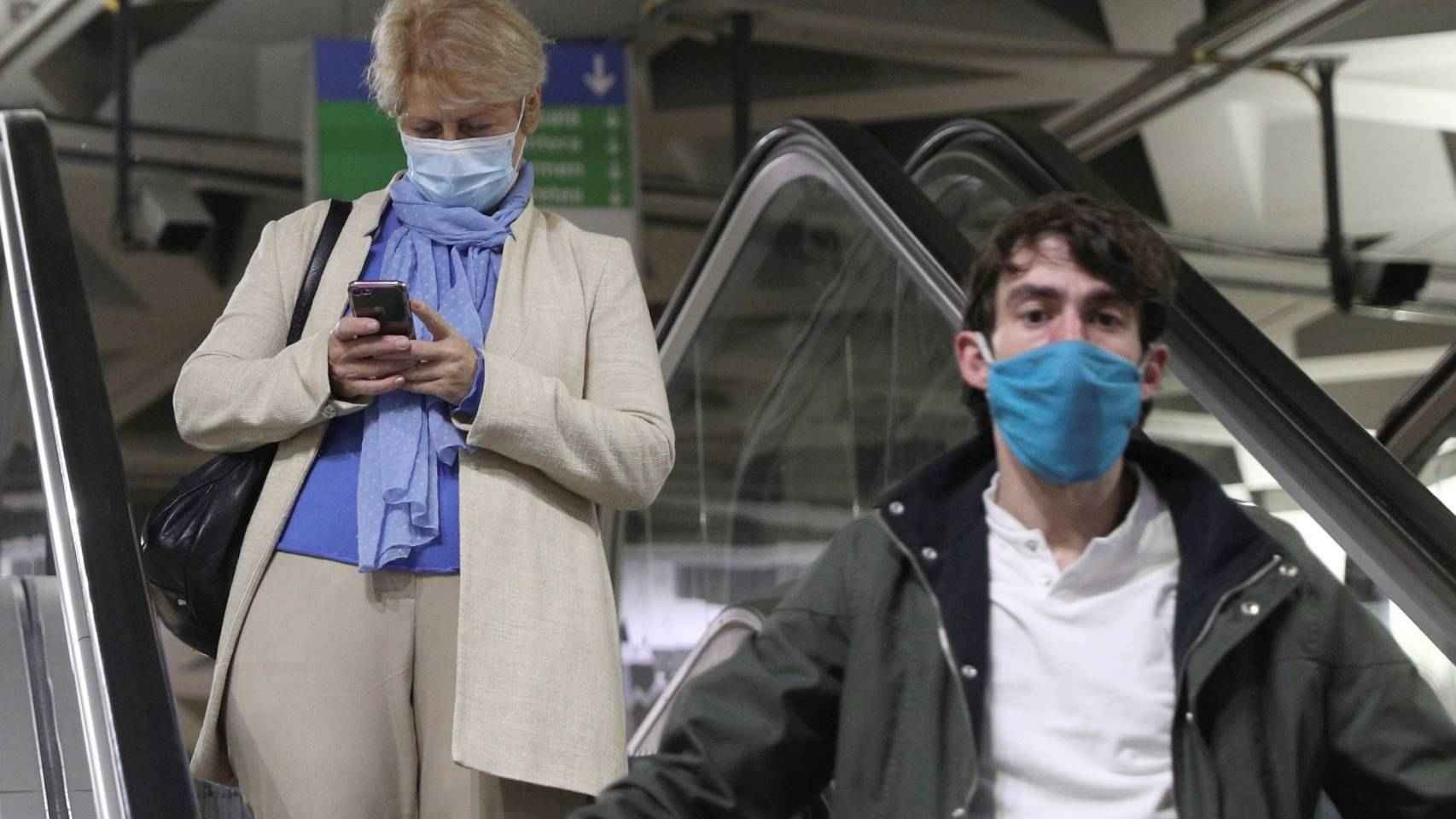 Ciudadana con mascarilla usando un móvil.