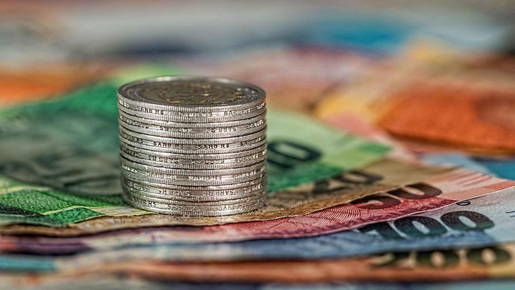 Moneda y billetes en un imagen de archivo.