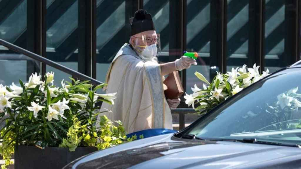 El padre Tim Pelc bendice a los fieles que se encuentran dentro del coche.