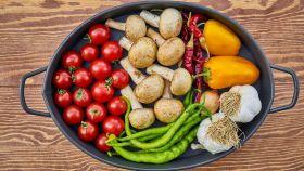 Una bandeja con verduras y champiñones.