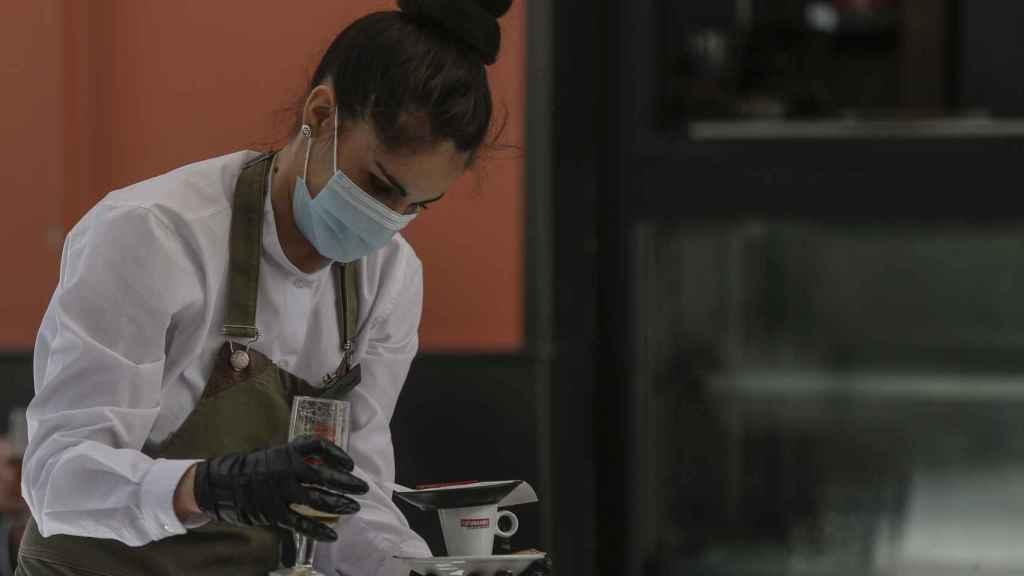 Una camarera con mascarilla y guantes.