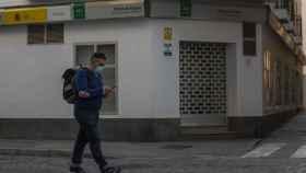 Un hombre protegido con mascarilla camina delante de una oficina de empleo.