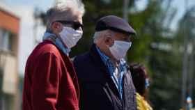Dos personas mayores llevando mascarilla por la calle.