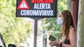 Una mujer espera el autobús junto a un panel informativo en Sevilla.