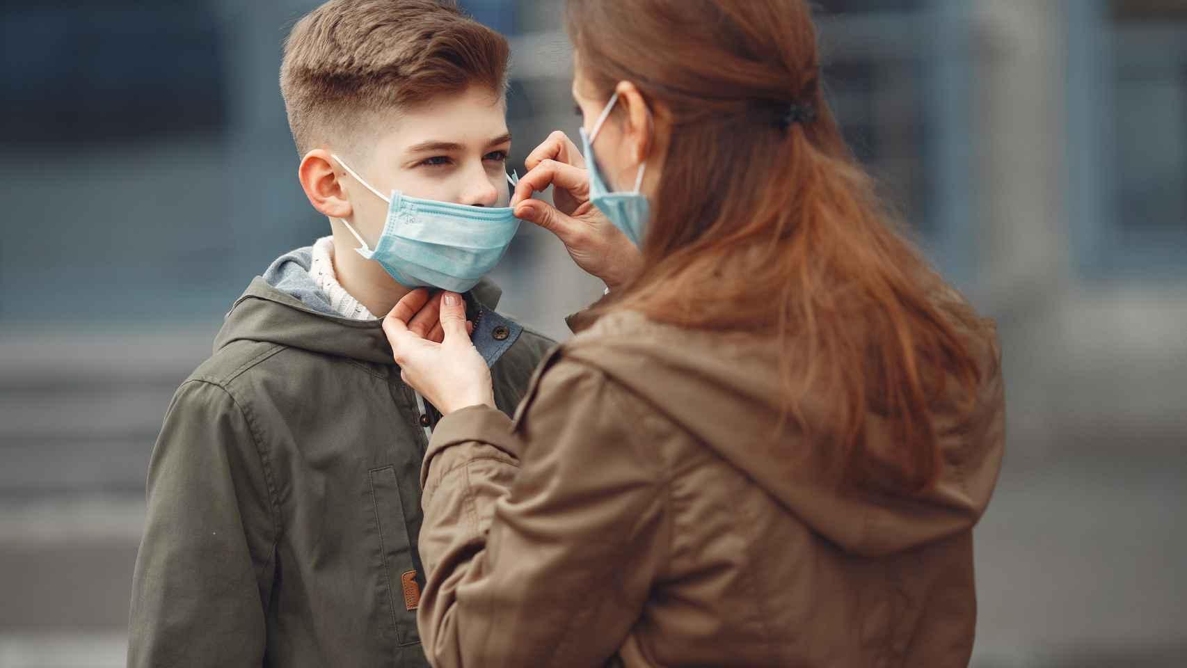 Una mujer coloca la mascarilla a un niño.