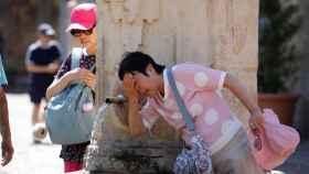 Turistas extranjeros se refrescan en una fuente en Sevilla.