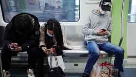 Prsonas con mascarilla usando un smartphone.