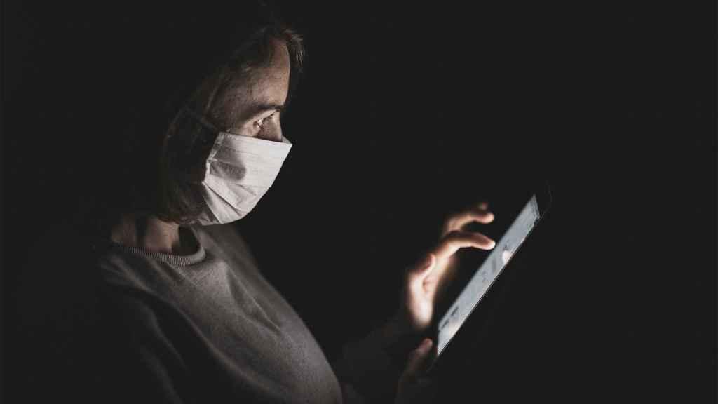 Persona usando un smartphone con mascarilla.