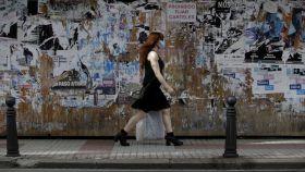 Una mujer con mascarilla camina por una céntrica calle de A Coruña.