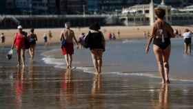 Paseo por la playa de La Concha de San Sebastián manteniendo la distancia de seguridad. EFE/Juan Herrero.