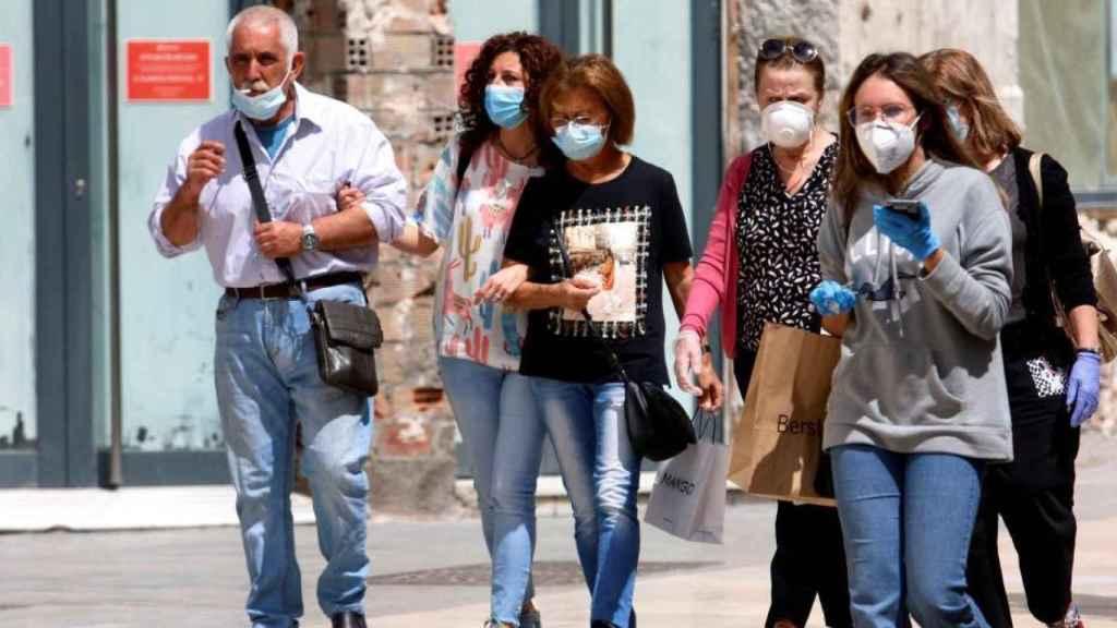 Un grupo de personas haciendo uso de la mascarilla obligatoria, pero con poca distancia social.