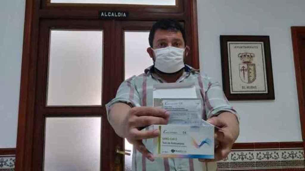 El alcalde de El Rubio (Sevilla), Rafael de la Fe, este jueves, sostiene una caja con los test rápidos que ha adquirido.