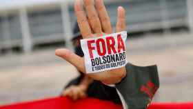 Un manifestante muestra una pegatina en la que se puede leer 'Bolsonaro,  fuera', durante una protesta en Brasilia.