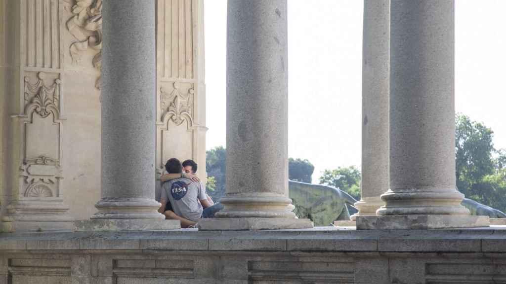 Una pareja en las columnas del monumento a Alfonso XII.