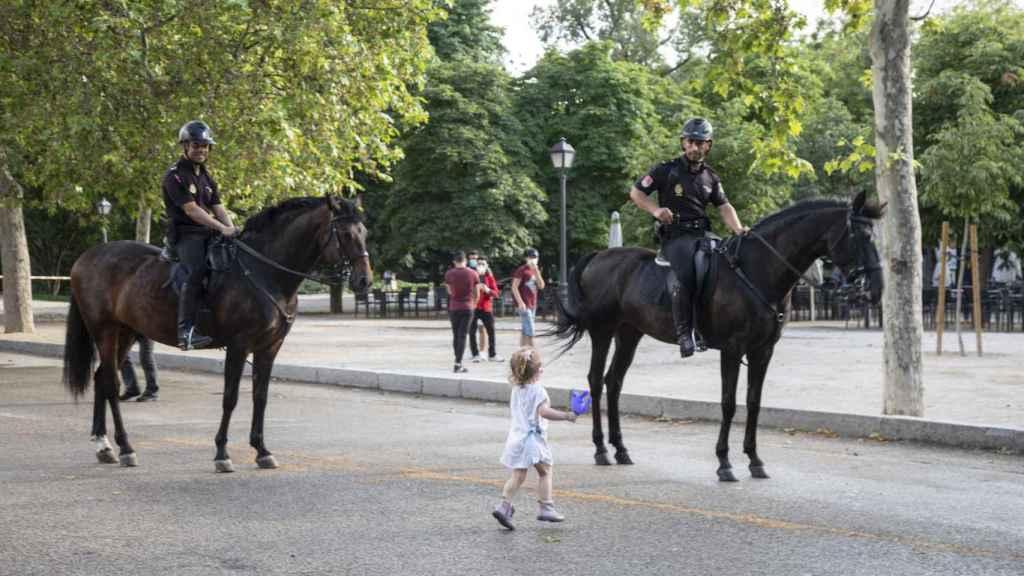 Una niña junto a policías a caballo, este lunes en el Parque del Retiro.