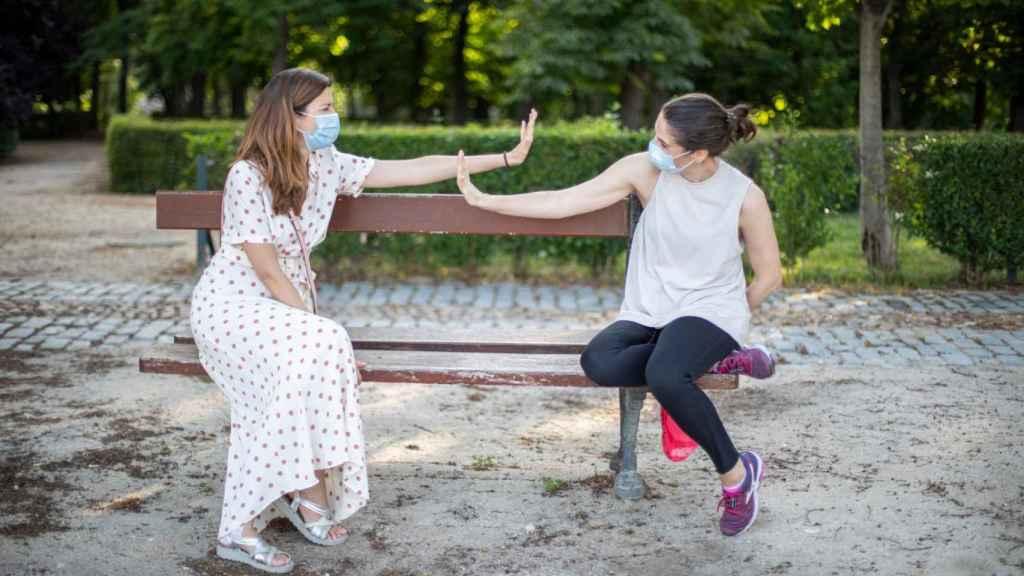 Dos amigas simulan saludarse sentadas en un banco del céntrico parque madrileño.
