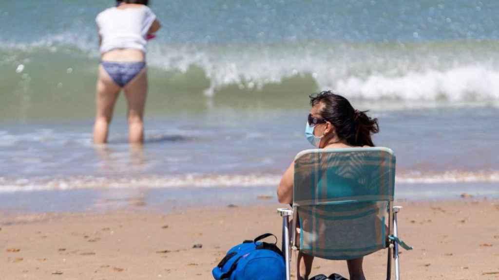 Una mujer con mascarilla en la playa de San Fernando, en Cádiz.