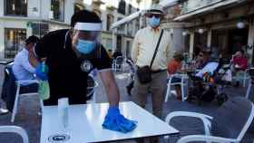 Un camarero desinfecta una mesa en un bar del centro de Málaga.
