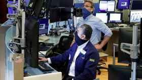 Dos operadores con mascarilla en la Bolsa de Nueva York.