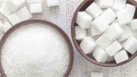 Dos cuencos de azúcar, uno en terrones y otro en pequeños cristales.