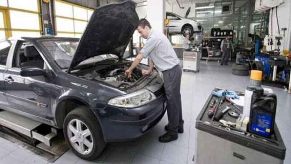 Un mecánico, revisando el motor de un vehículo.