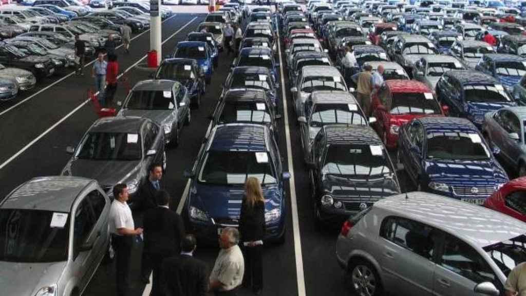Un grupo de personas observando coches en concesionario.