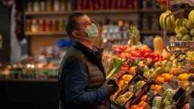 Un hombre protegido con mascarilla es atendido en una frutería.