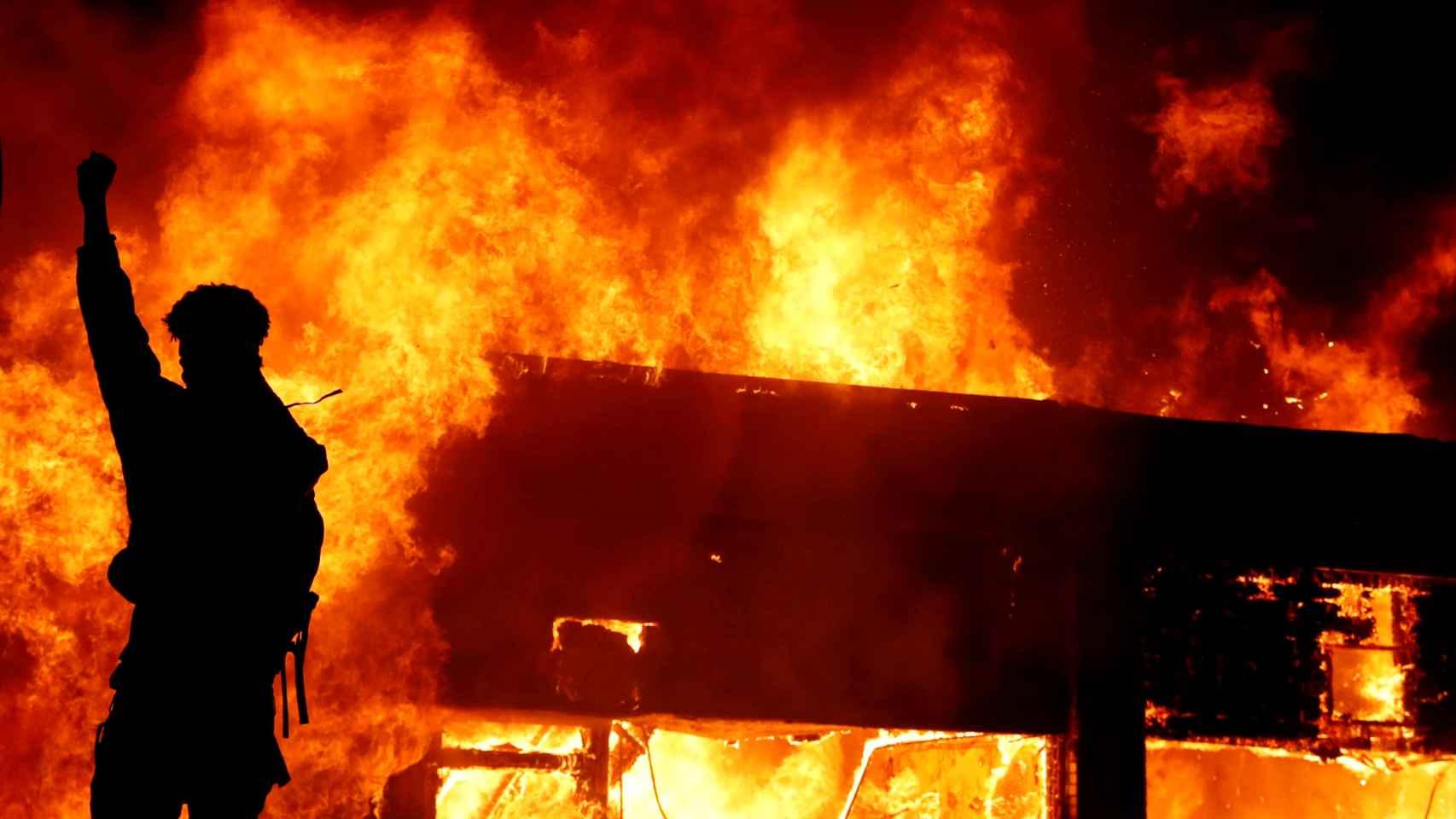 Un manifestante frente al incendio de un edificio en Minneapolis.