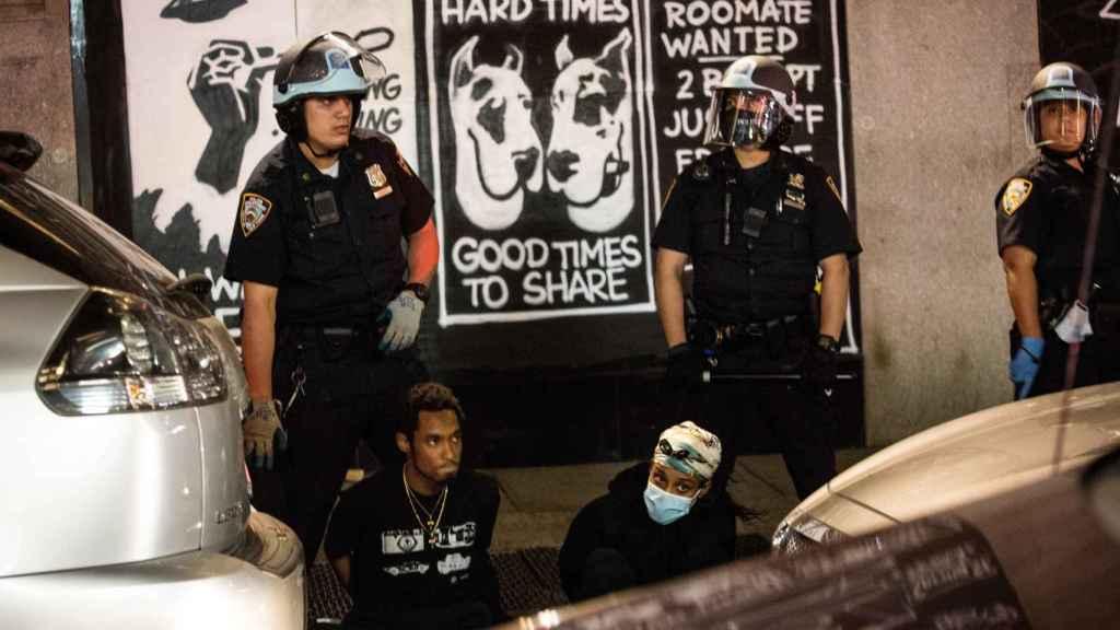 Policías custodian a dos detenidos.
