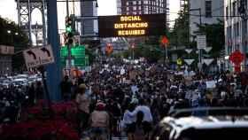Marcha en Nueva York. Los paneles luminosos instan al distanciamiento social.